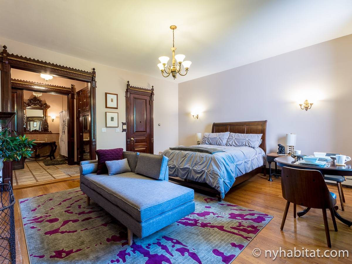 Image of the bedroom of alcove studio vacation rental NY-17657 in Harlem with bed and lounge with antiques and ornate woodwork in the background