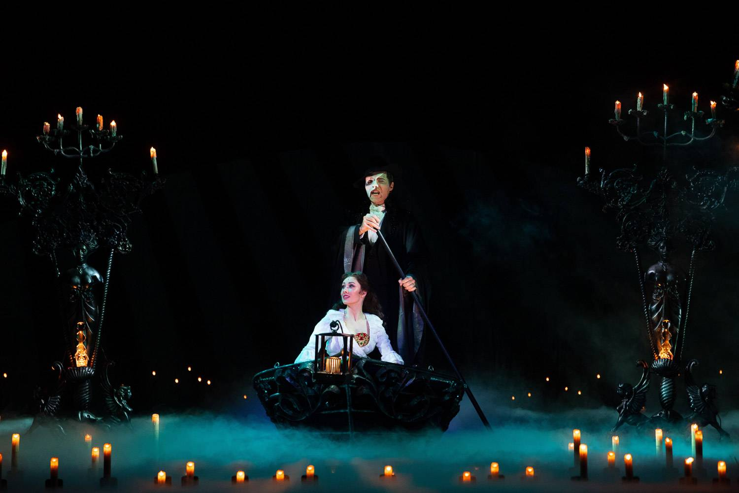 Image from Phantom of the Opera on Broadway with the main characters in a boat in the dark surrounded by candles
