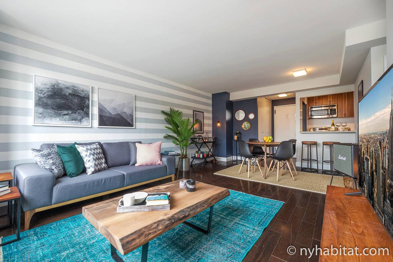 Image of living room with wood coffee table and plants with dining area and kitchen in the background in Upper East Side furnished rental NY-17624