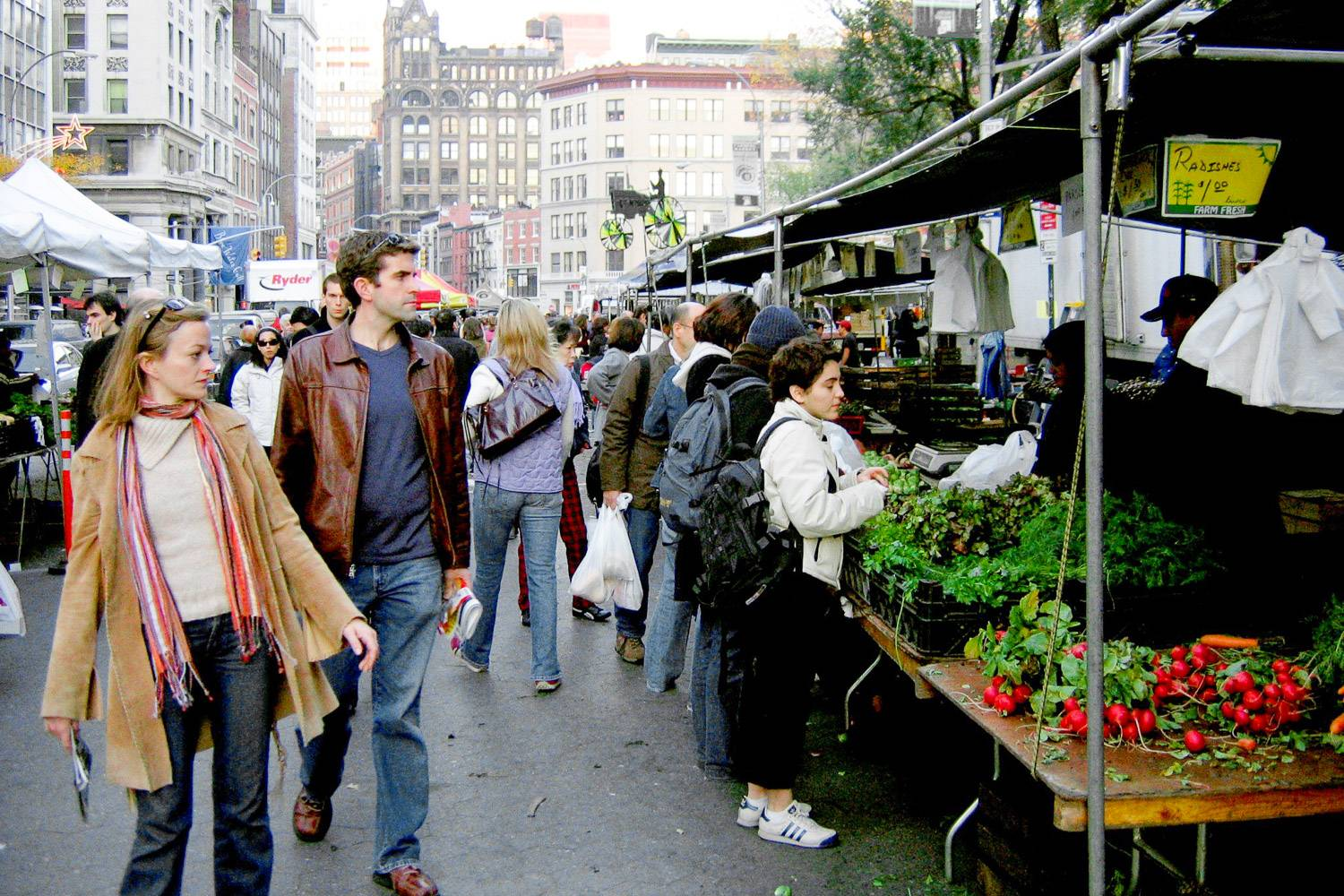 Image of people shopping in the Union Square farmers market with stalls of vegetables around and NYC buildings in the background