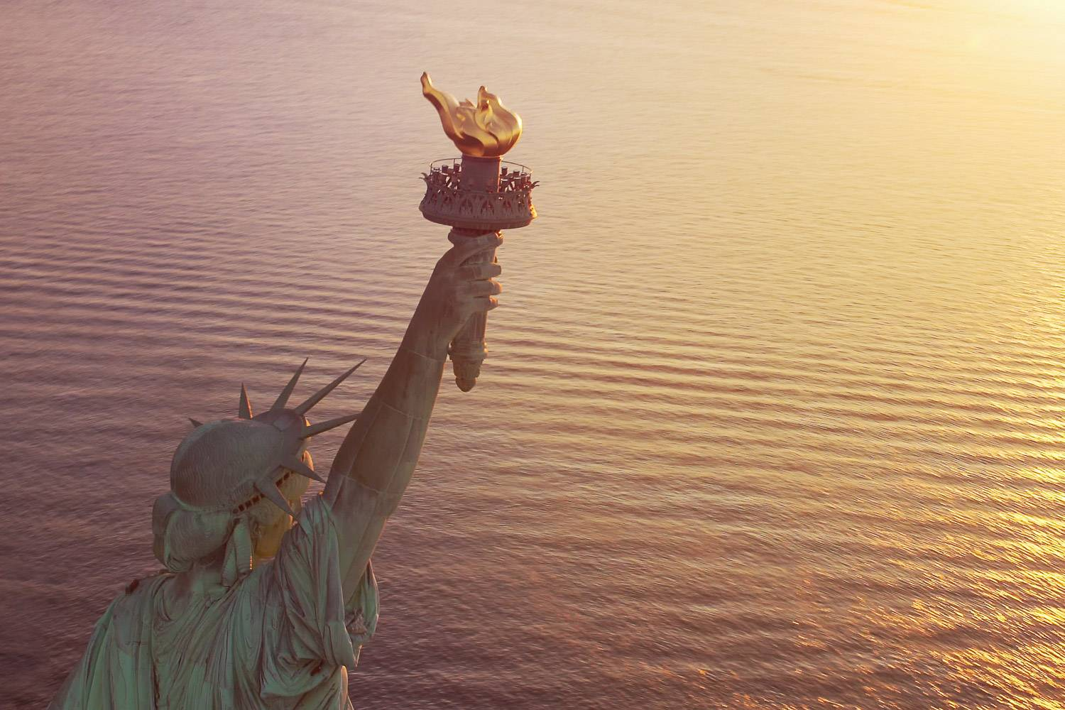 Image of the Statue of Liberty with golden torch above the water close up at sunset