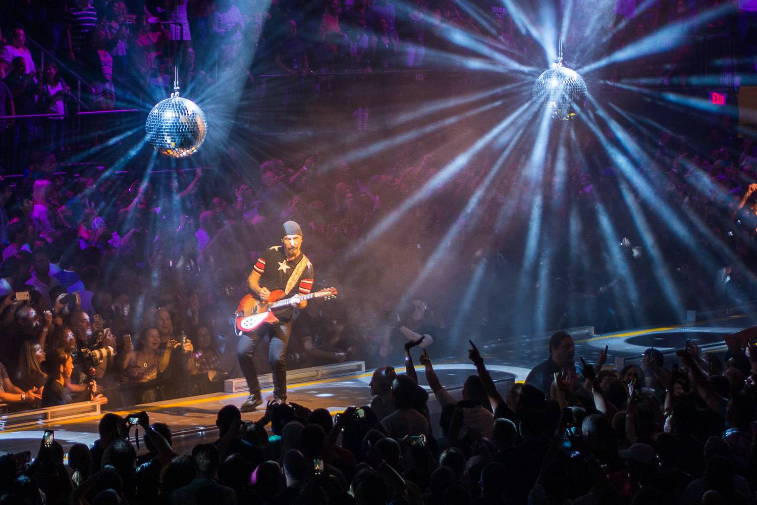 Image of rock band U2 playing at Madison Square garden in NYC with disco balls hanging from the ceiling