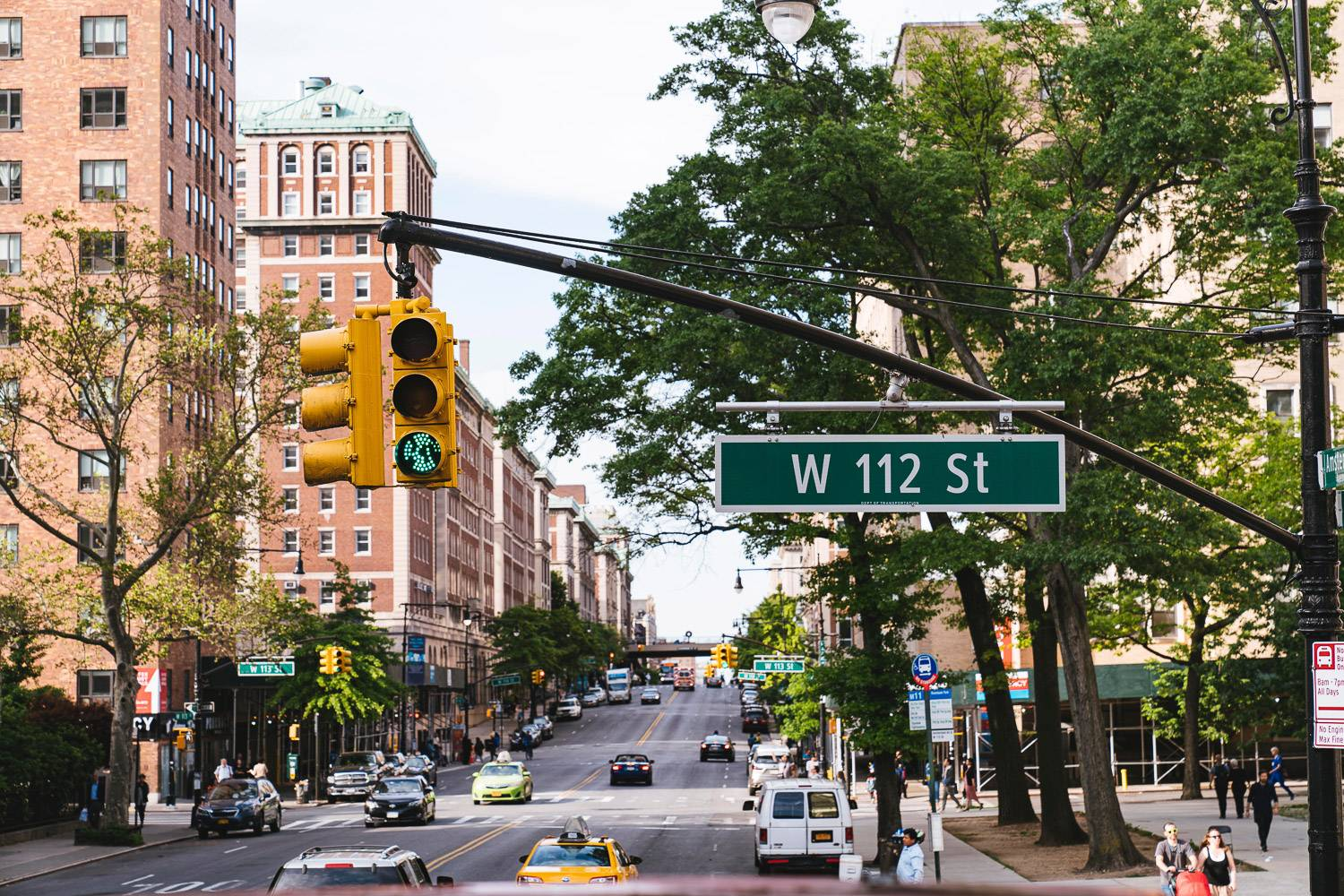 Image of an avenue in NYC with traffic lights and a street sign with West 112th Street