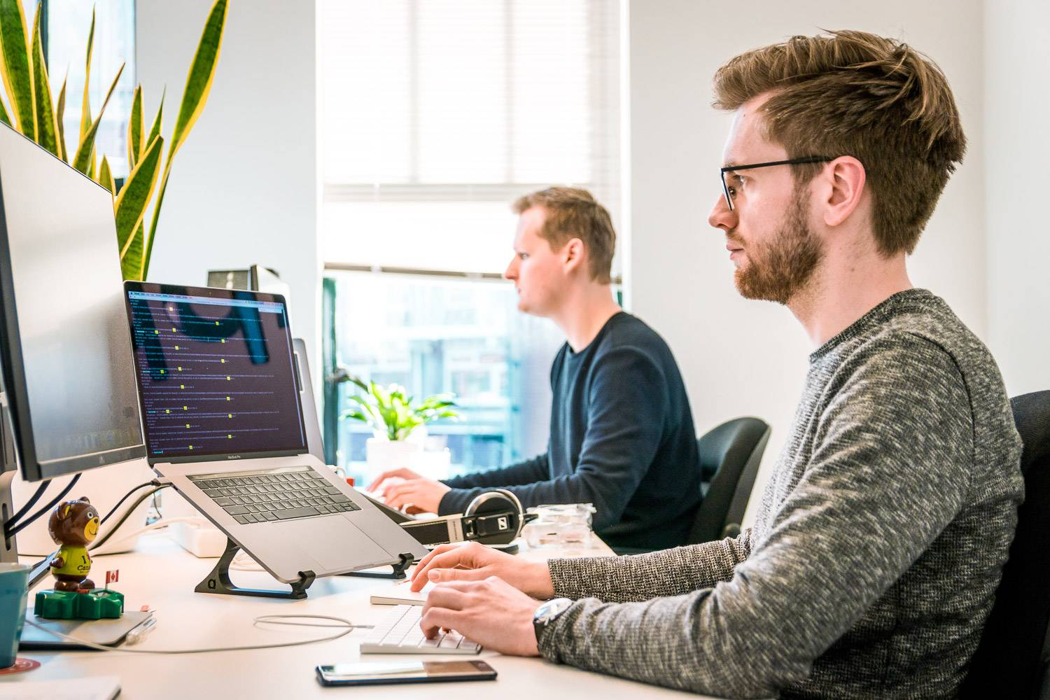 Image of two men on computers in an office