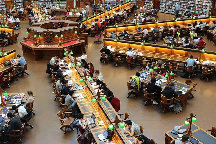 Image of a large library with students studying