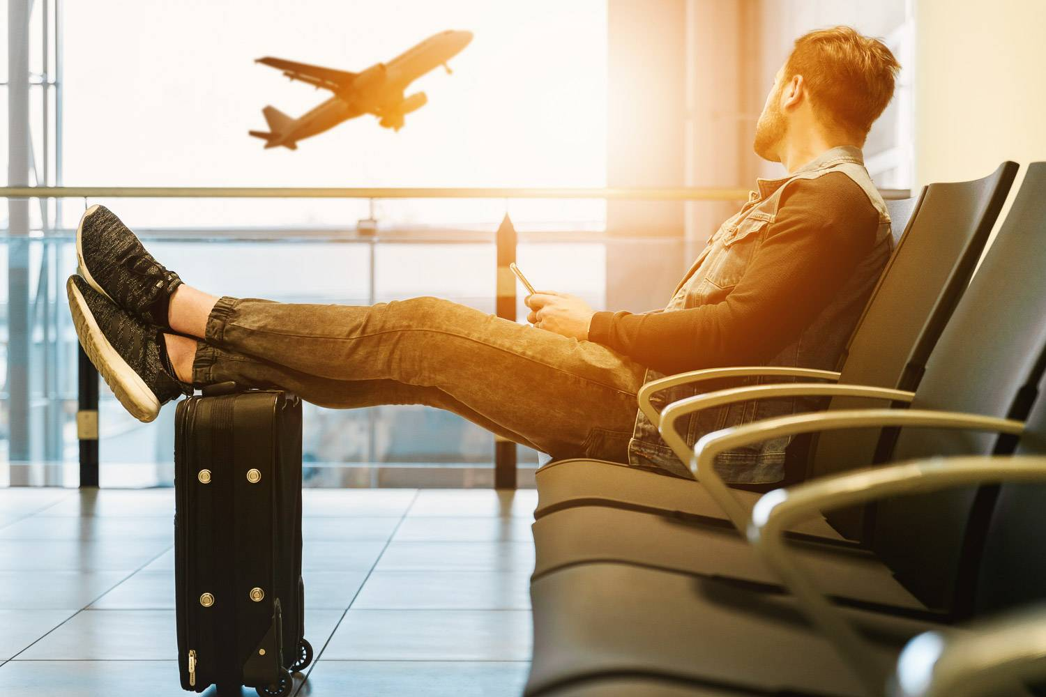 Image of male sitting in an airport with luggage and plane taking off out the window