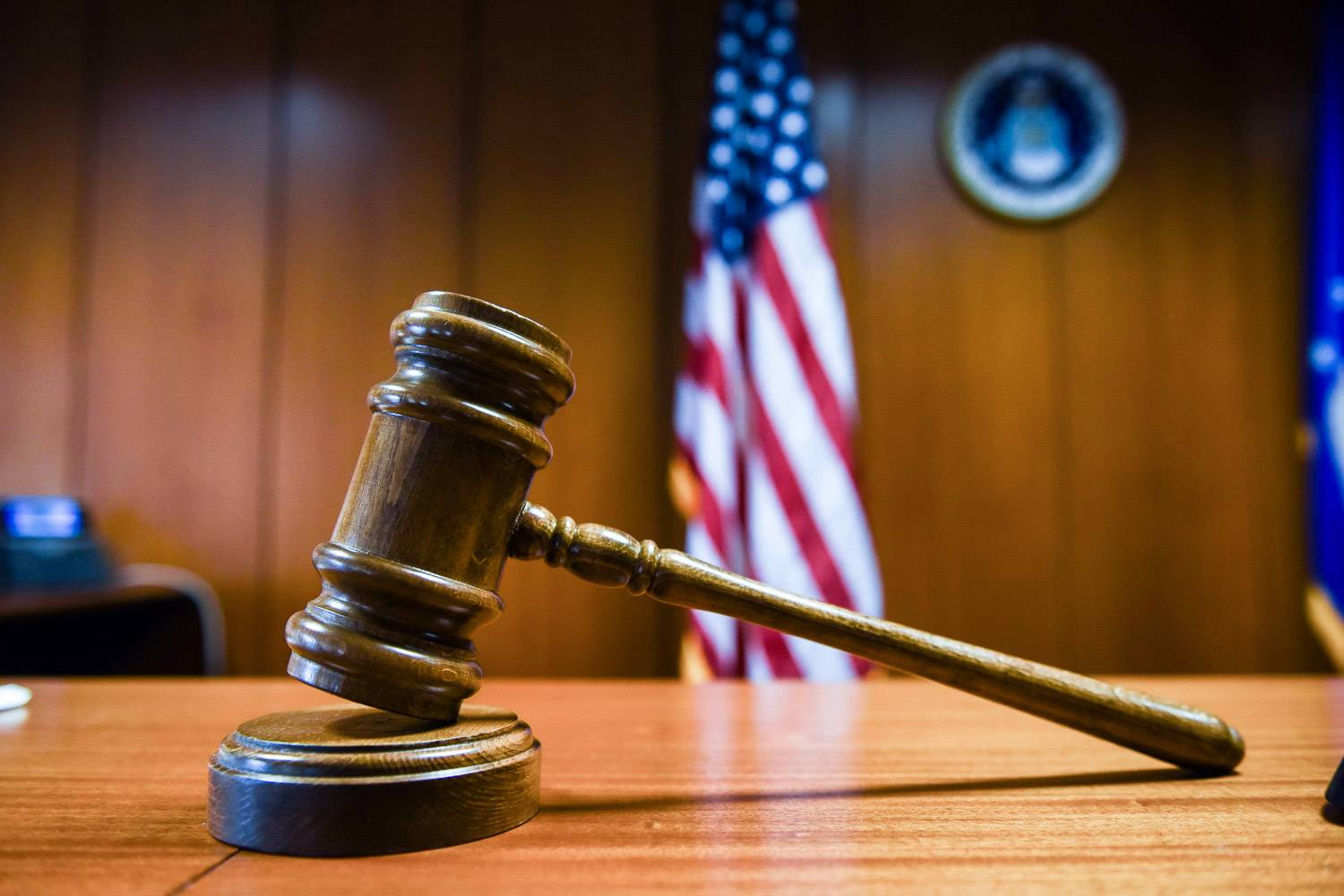 Image fo a gavel on a court bench with American flag in the background