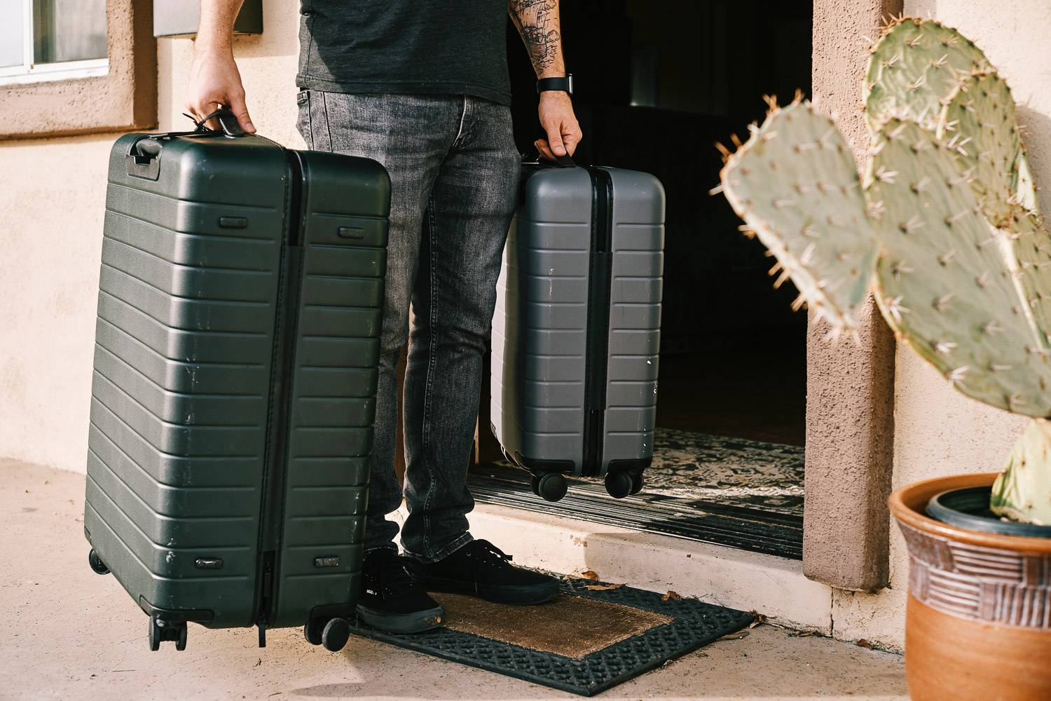 Image of a man carrying two suitcases entering a house