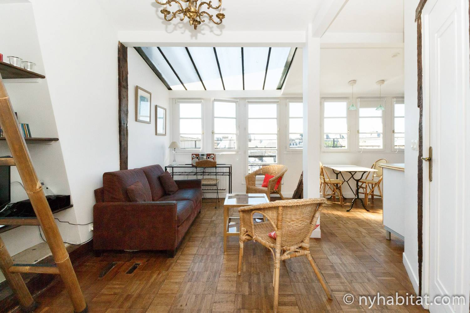Image of the living room of furnished apartment PA-2473 in Saint-Germain des Prés showing a door opening onto the balcony in the background, seven other windows and a skylight.