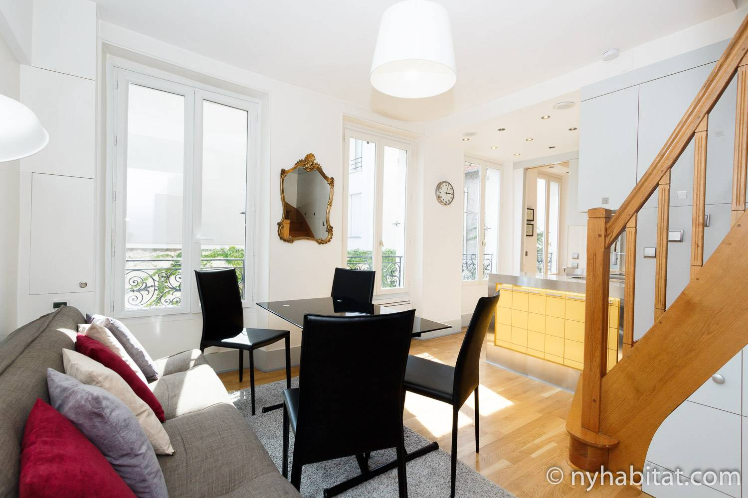 Image of the living room of furnished apartment PA-4335 in Belleville, Paris showing 4 win-dows and stairs going to the upper level.