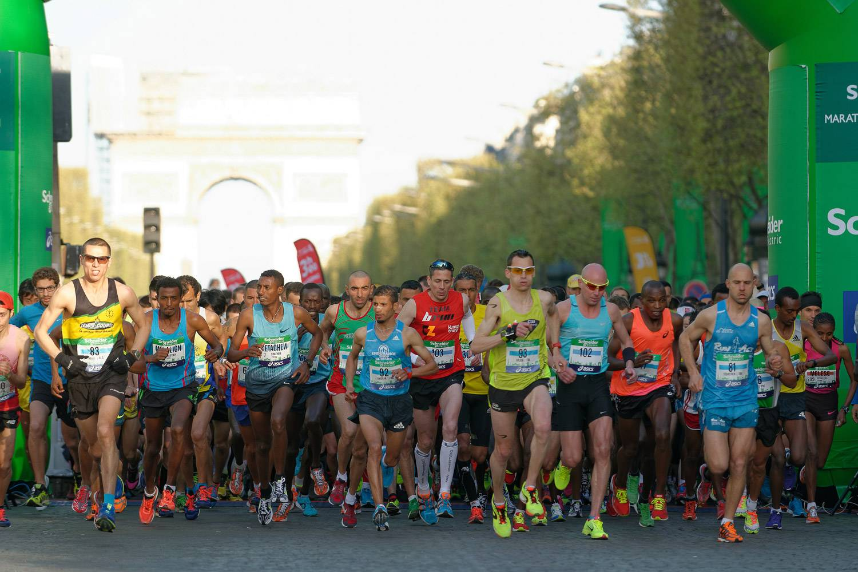 Photo of the Paris Marathon participants running down the Champs-Elysées Avenue with the Arc de Triomphe in the background.