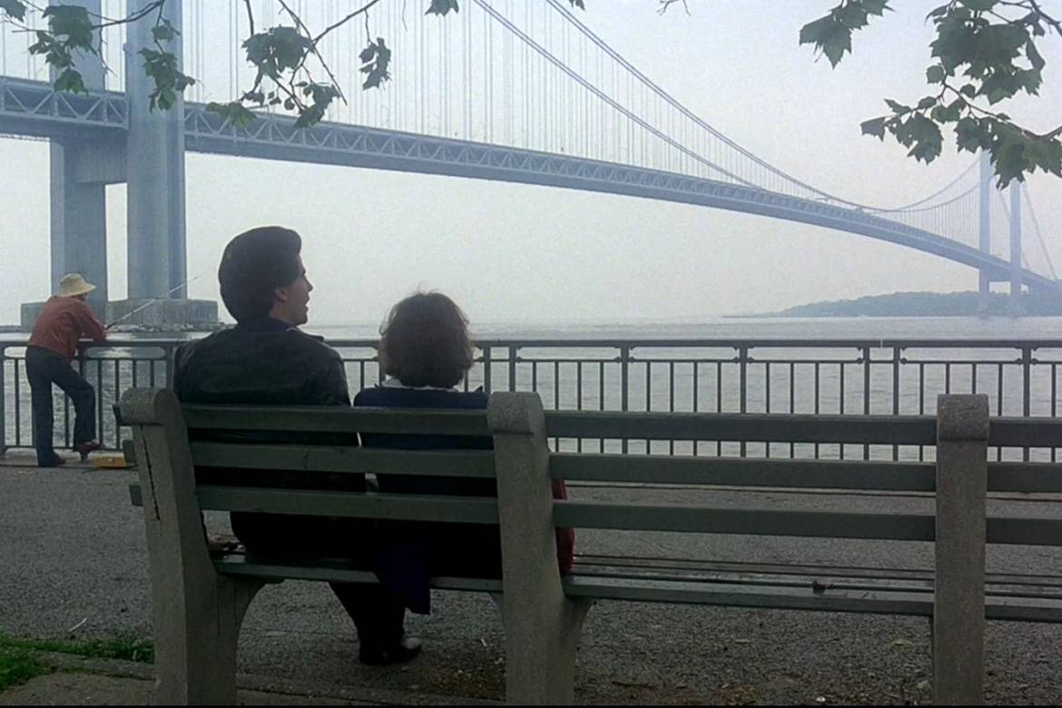 Standbild von John Travolta und Karen Gorney vor der Verrazano-Narrows Bridge in Saturday Night Fever.