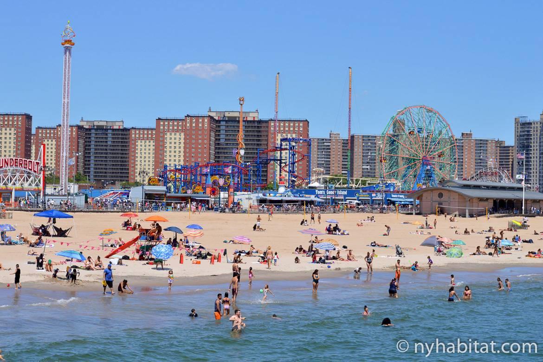 Bild vom Strand in Coney Island mit Schwimmern, der Strandpromenade und Luna Park im Hintergrund.