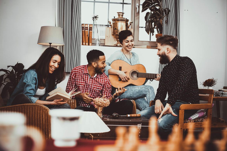 Bild von jungen Mitbewohnern, die zusammen Musik in Ihrer gemeinschaftlichen Wohnung spielen.