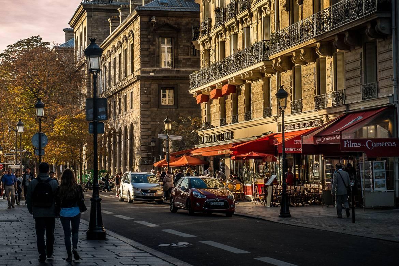 Bild von Menschen, die die Rue du Cloitre in der Abenddämmerung entlanglaufen.