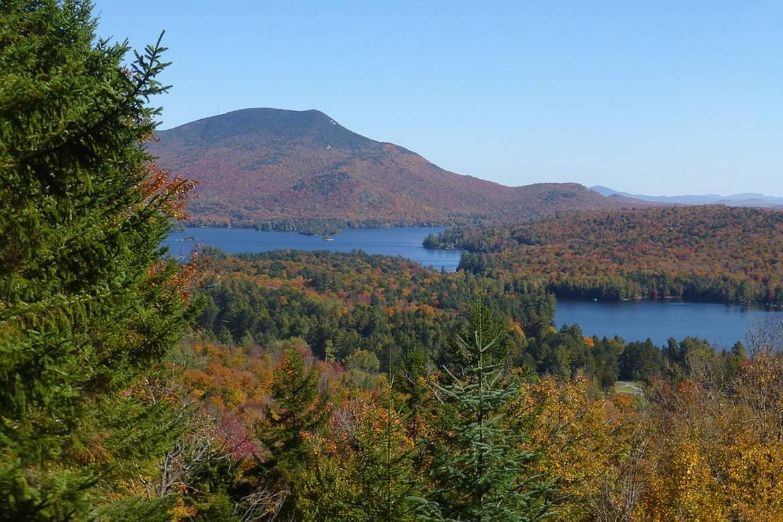 Bild von den Adirondack Mountains im Herbst, die einen See umgeben.