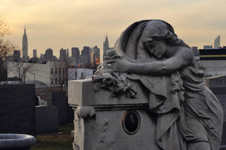 Foto eines Grabes mit Statue auf dem Cavalry Friedhof in Queens, New York während des Sonnenuntergangs.