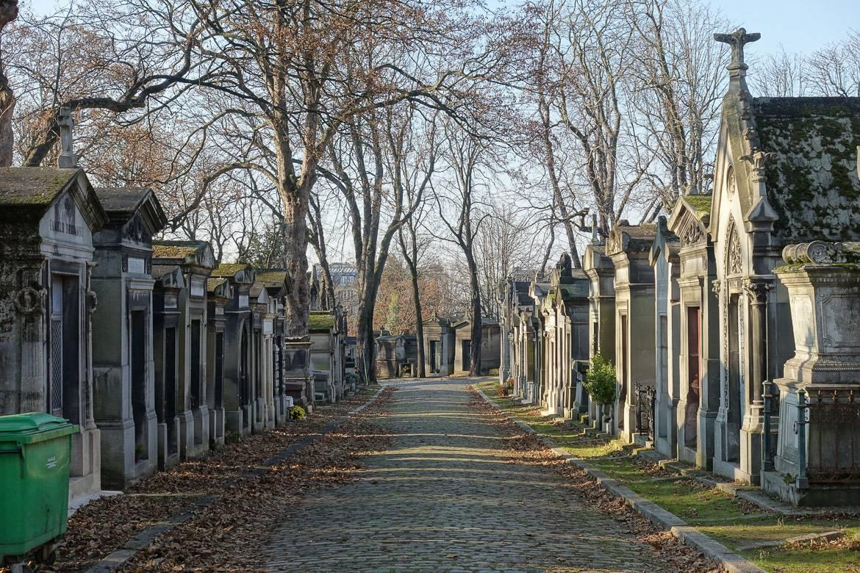 Foto von einem Steinweg und Mausoleen auf dem Père Lachaise Friedhof in Paris.