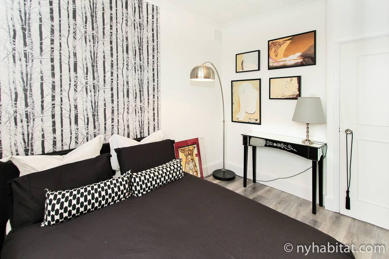 Bild von einem Schlafzimmer in LN-1209 mit Doppelbett, einer Lampe und Kunst.