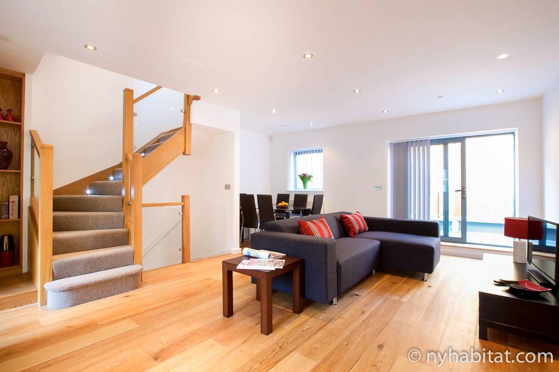 Bild vom Wohnzimmer in LN-1290 mit Sofa, Esstisch und Treppen.