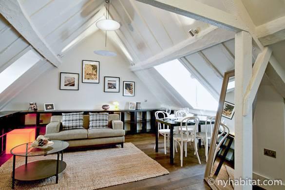 Bild von einem Wohnbereich in LN-1400 mit Sofa, Esstisch, Kunstwerken und Dachfenstern.