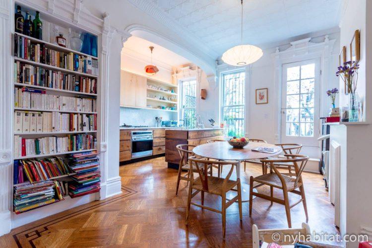Foto des Esszimmers in NY-15804 mit Esstisch, Stühlen, Kronleuchter und Bücherregalen.