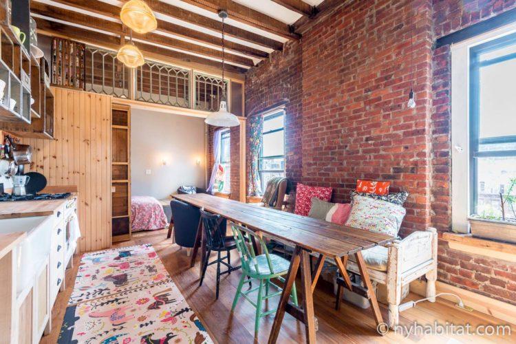 Foto vom Wohnzimmer und der Essecke in NY-17495 mit Esstisch, verschiedenen Sitzmöglichkeiten und Arbeitsplatte in der Küche.