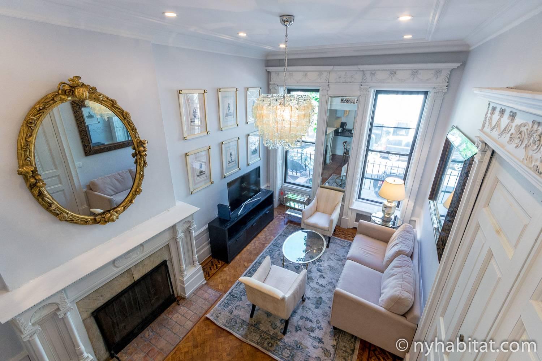 Foto des Wohnzimmers in NY-16873 mit Kamin, Sofas, hohen Decken und Kronleuchter.