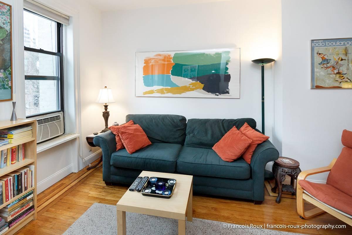 Foto des Wohnzimmers in NY-16166 mit Sofa und Kunstwerken an den Wänden.