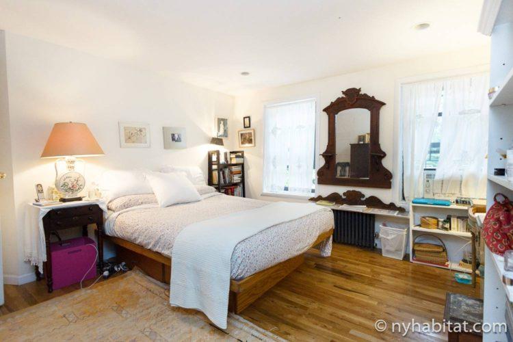 Bild des Schlafzimmers in NY-16507 mit Doppelbett und Bücherregalen.