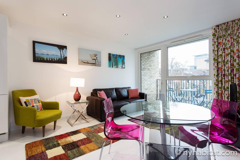 Bild vom Wohnbereich in LN-1966 mit Sofa, Esstisch, Stühlen und Tür zum Balkon.