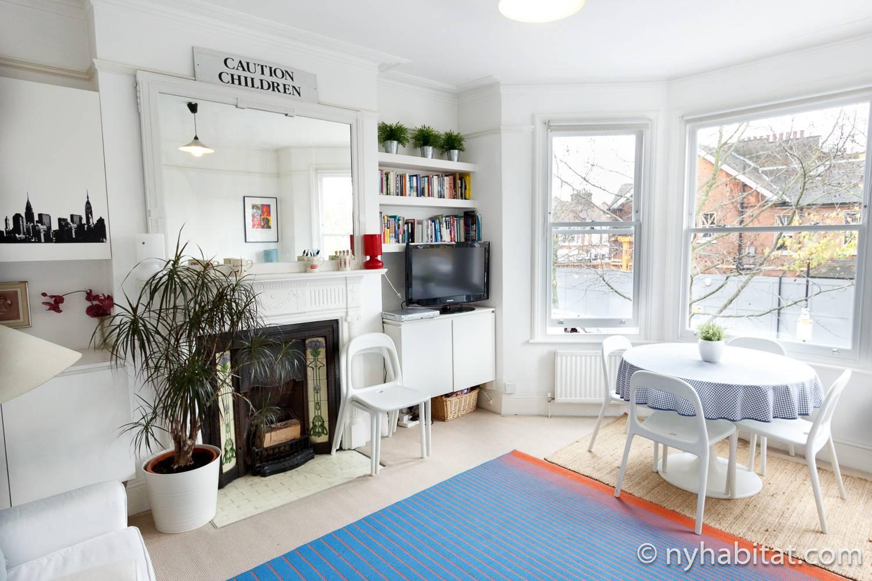 Foto des Wohnzimmers der Wohnung LN-486 mit Esstisch und Stühlen, Kamin und Bücherregal.