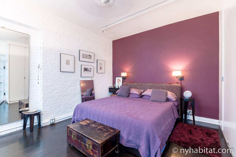 Foto des Schlafzimmers in der NY-12330 mit King-Size-Bett, Beistelltischen und Kunstwerken.