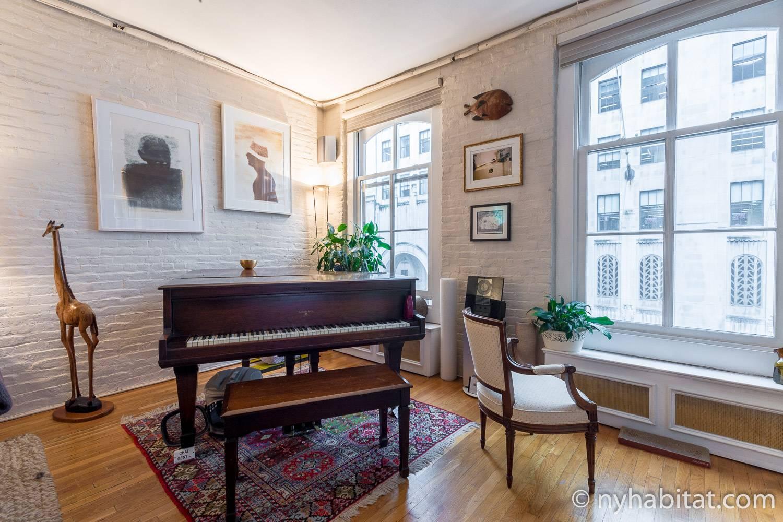 Foto des Wohnbereichs in der NY-12330 mit Flügel, Fenstern und Kunstwerken.