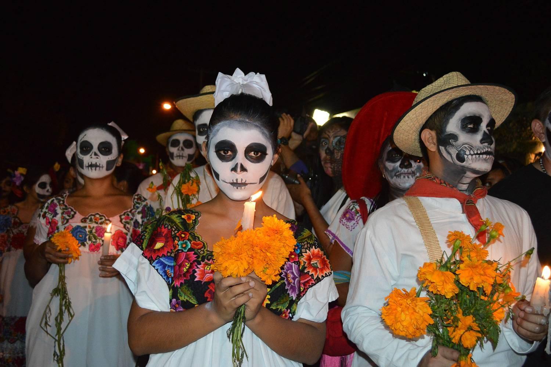 Bild von Menschen, die wie Skelette geschminkt sind und für den Día de los Muertos Kerzen tragen.