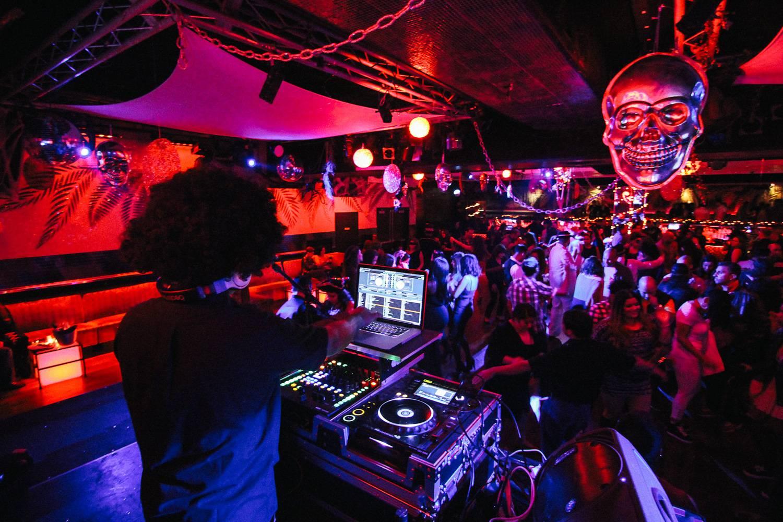 Bild von einem DJ, Halloween-Dekorationen und tanzenden Menschen im Copacabana Nachtclub in NYC.