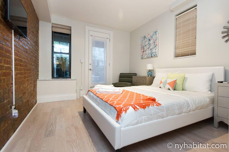 Bild des Schlafzimmers in NY-16635 mit Doppelbett und Fernseher.