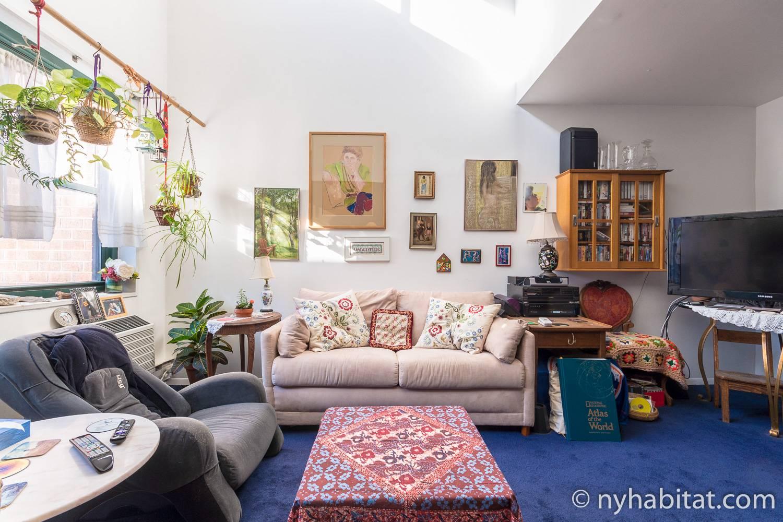 Bild des Wohnbereiches in NY-17088 mit Sofa und Kunstwerk.