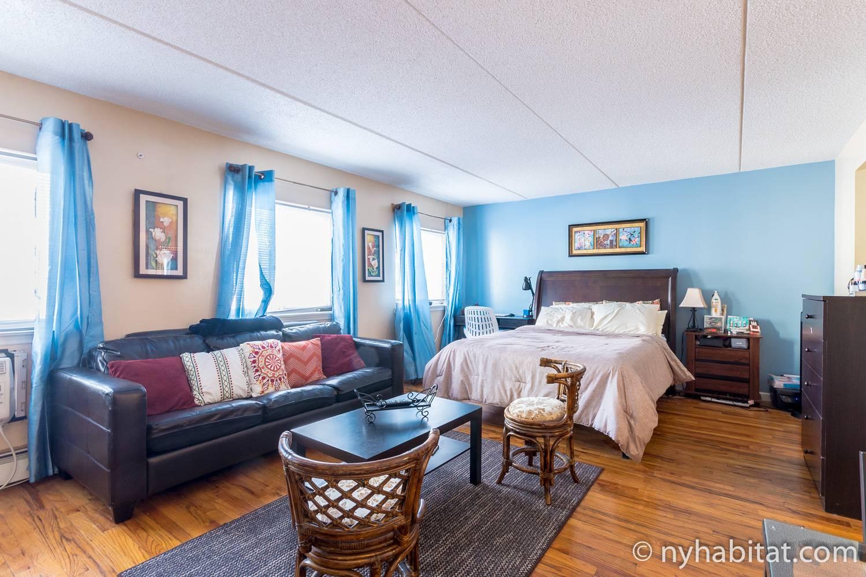 Bild des Wohnbereichs in NY-17370 mit Sofa, Vorhängen und Queen-Size-Bett.