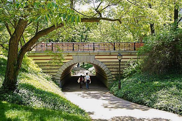 Bild von einem Pärchen, das zur Sommerzeit durch eine von Central Parks vielen Bogenbrücken läuft.