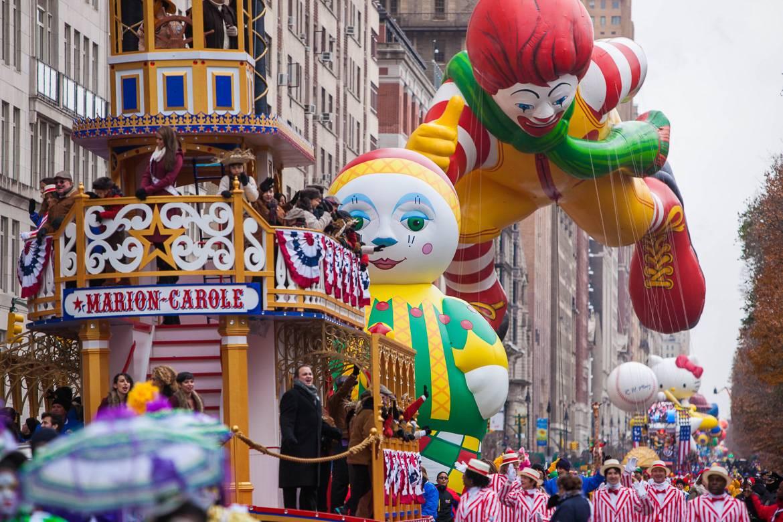 Abbildung von Ballons und Umzugswagen bei der Macy's Thanksgiving Day Parade.
