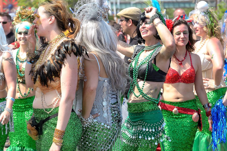 Abbildung von marschierenden Leuten auf der Coney Island Mermaid Parade in Meerjungfrauenkostümen.
