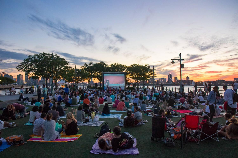 Abbildung einer Filmvorführung im Freien im Hudson River Park bei Abenddämmerung.