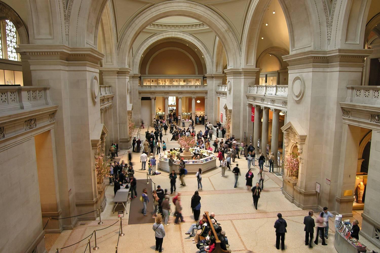 Abbildung der Eingangshalle des Metropolitan Museum of Art, voll mit Gästen.