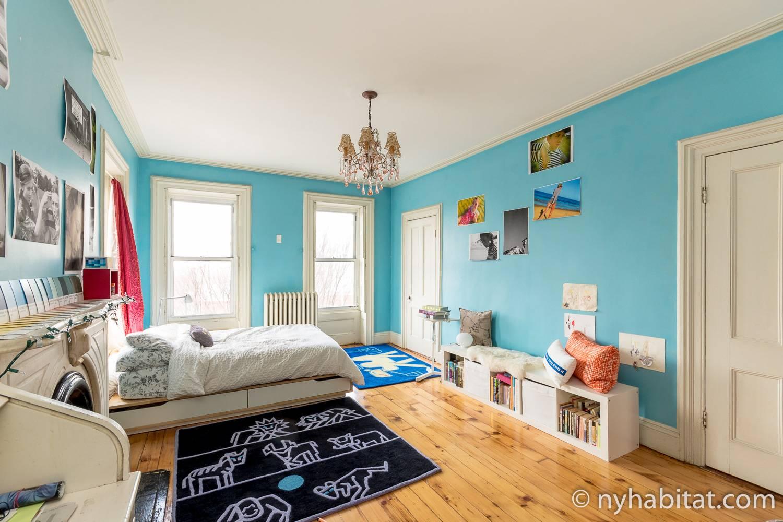 Abbildung des Schlafzimmers in NY-14369 mit Doppelbett, Kronleuchter und Kunstwerken.