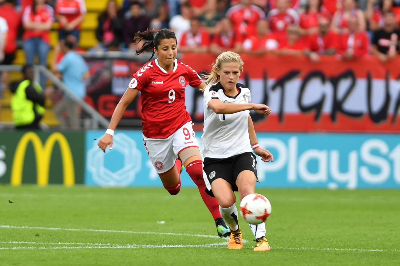 Bild von zwei Fußballspielerinnen aus Dänemark und Österreich während eines Spiels.