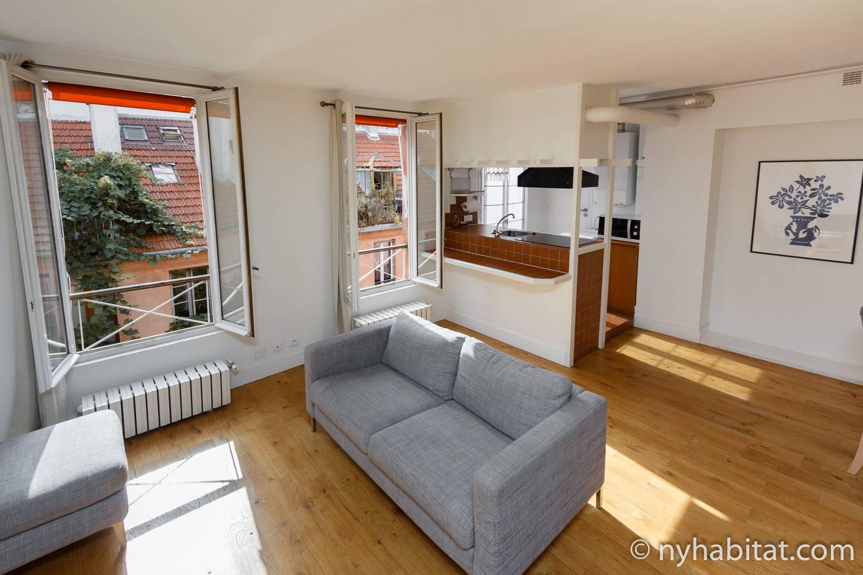 Bild des Wohnbereichs in PA-4399 mit einer grauen Couch.