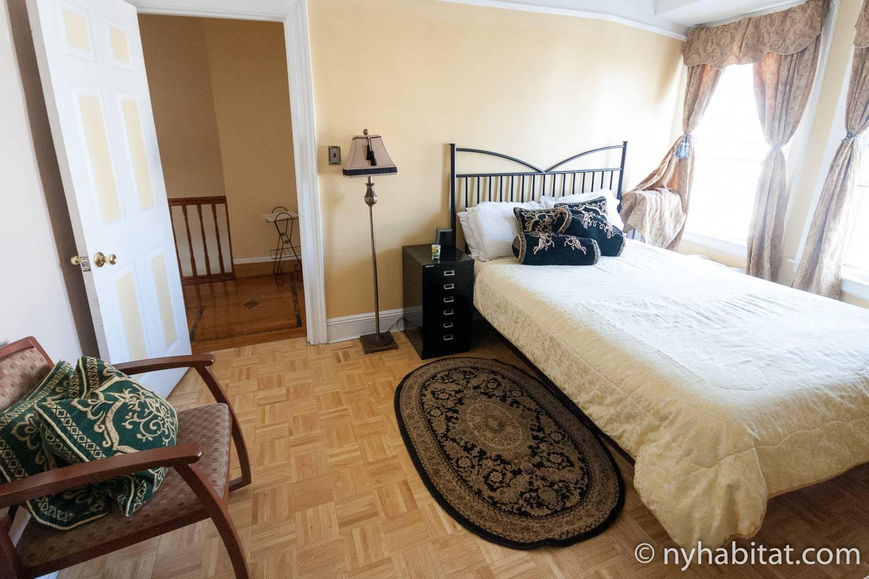 Foto des Schlafzimmers in NY-16268 mit Einzelbett und Stuhl.