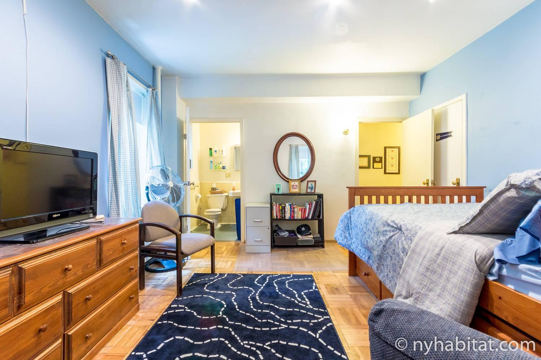 Foto des Schlafzimmers in NY-17206 mit Doppelbett, Kommode, Bücherregal und eigenem Badezimmer.