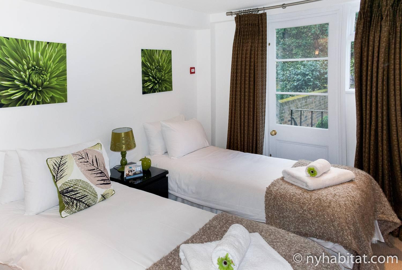 Bild des Schlafzimmers in der Mietwohnung LN-540 mit zwei Einzelbetten und einer Tür zum Garten.
